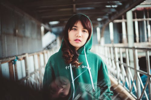 Woman in Green Hoodie Sweater Standing Near White  Metal Railings