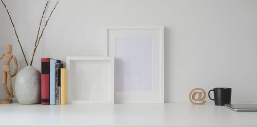 White Picture Frames and Books In Organized Display