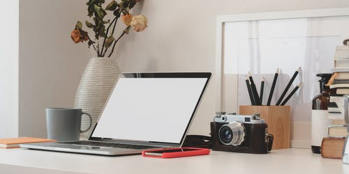 Analog Camera Behind Computer Laptop
