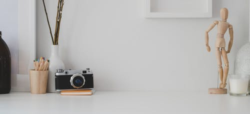 Black and Silver Camera on White Wooden Table