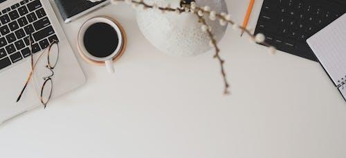 White Ceramic Mug and Vase on White Table  Beside Laptop