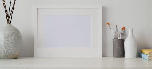 White Picture Frame on White Wooden Table Near Ceramic Vase