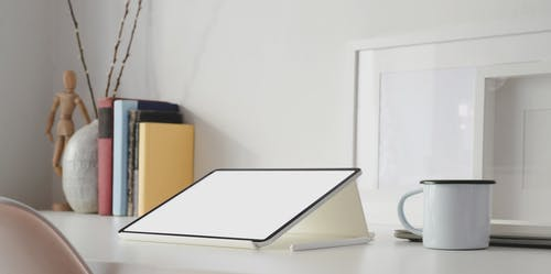 White Ipad on White Table Beside Ceramic Cup