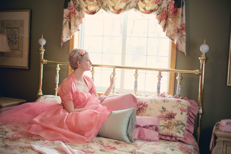 Woman Sitting on Bed Near Window