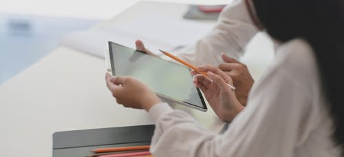 Person in White Long Sleeve Shirt Holding a Tablet and Pencil