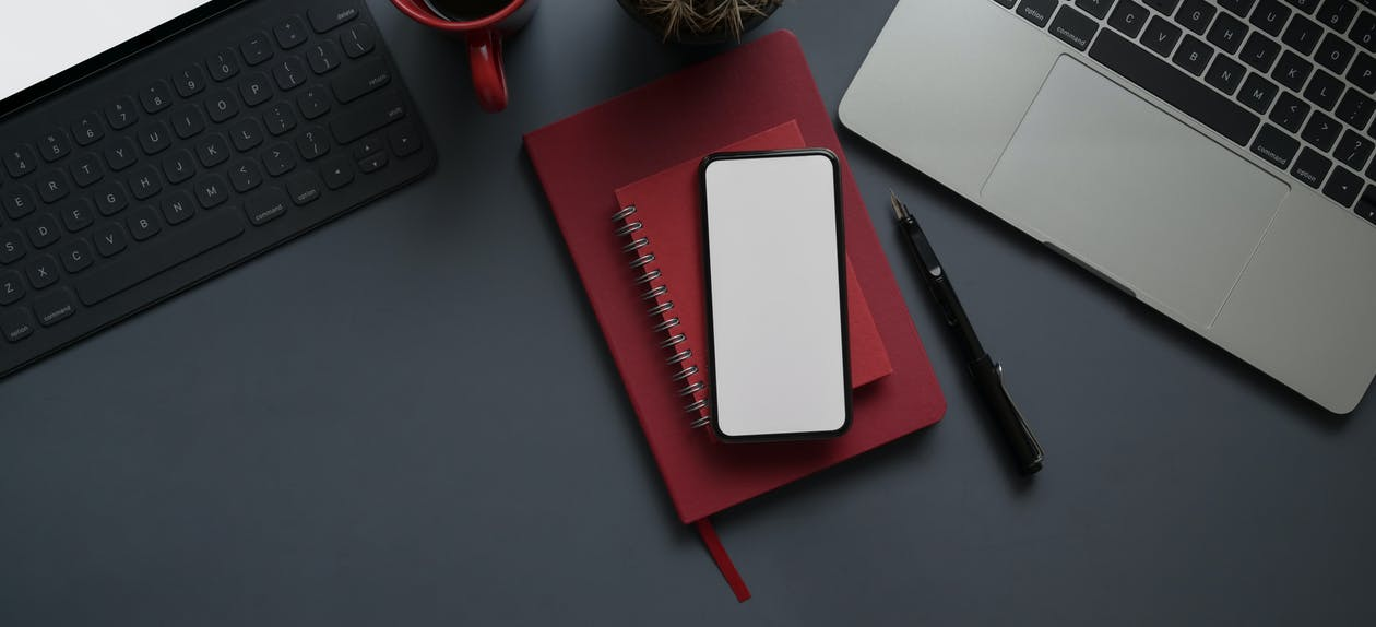 Red Notebook and Smartphone Beside Computer Laptop