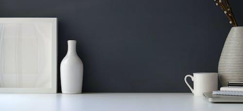 Wooden Frame Beside Ceramic Bottle Near Ceramic Cup and Vase on White Table