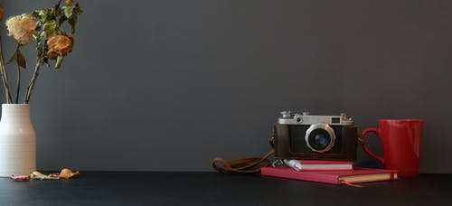Black and Silver Camera on Red Covered books