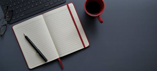 Notebook and Pen Beside Red Mug on Gray Surface