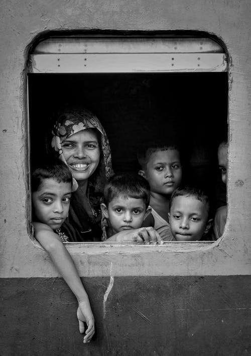 Ethnic kids in window of old train