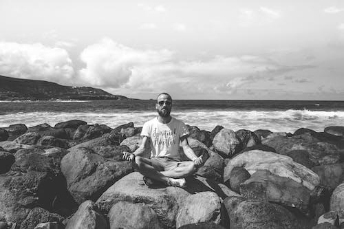 Grayscale Photo of Man Sitting on Rock Near Sea