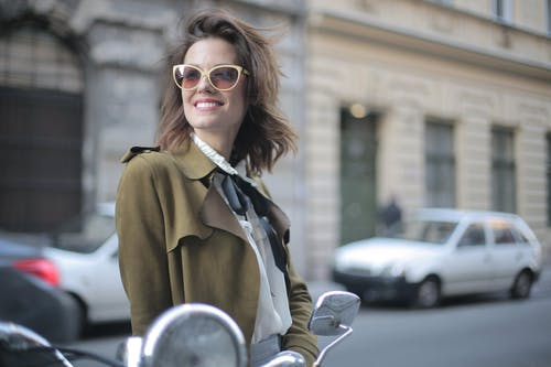 Happy adult female in trendy sunglasses and elegant clothes looking away and smiling while standing against blurred parked cars on sidewalk and exterior of old building in downtown