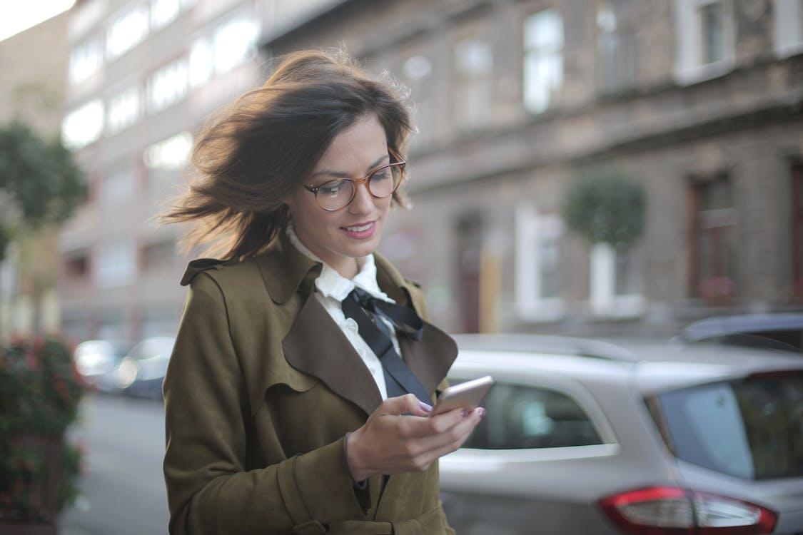 路上でスマートフォンを使用してスタイリッシュな大人の女性