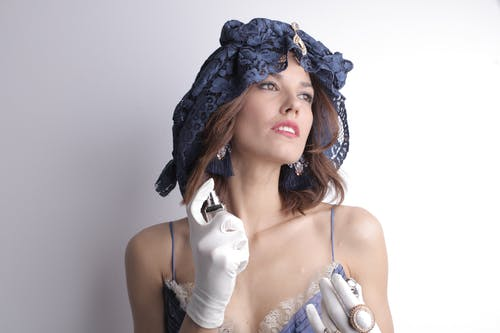 Charismatic sensual female in elegant vintage blue dress and lace headgear wearing white satin gloves and luxury bijouterie looking away and spraying fragrant perfume to delicate neck skin against white background