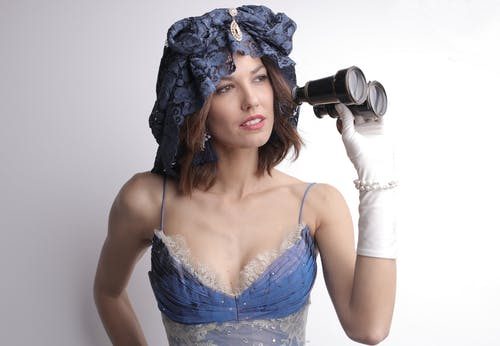 Pensive sensual woman in vintage outfit with binoculars