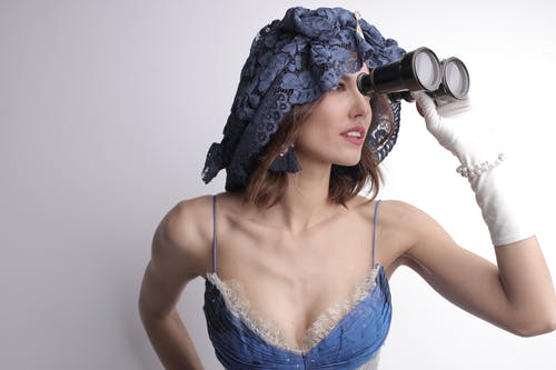 Magnificent young lady in blue dress and headdress in boho style wearing white gloves looking away with interest using binoculars while standing against white background in studio