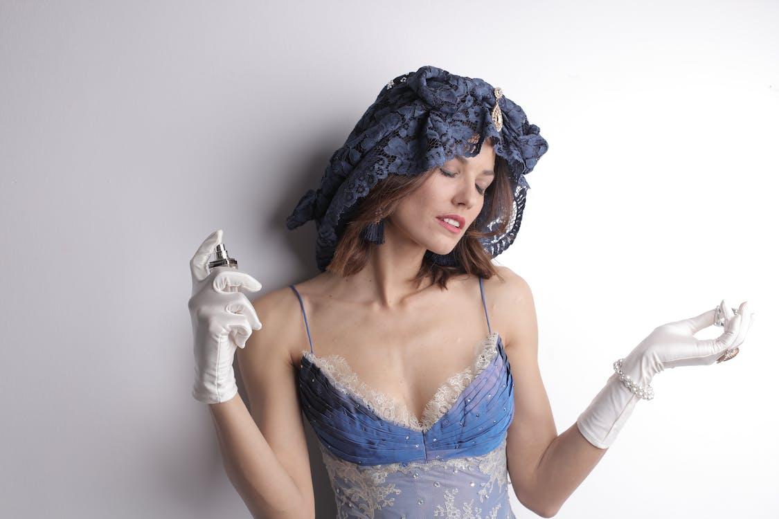 Woman in Blue Under Garments Spraying Perfume