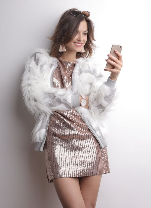 Woman in White Fur Coat Holding a Cellphone