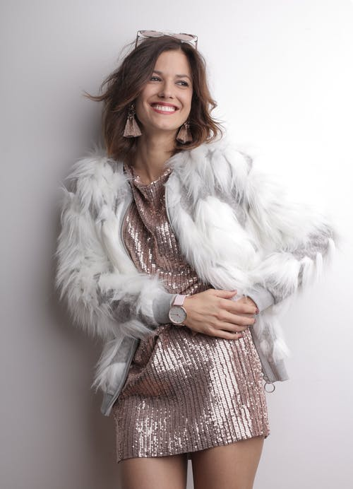 Woman in White Fur Coat Leaning on Gray Wall