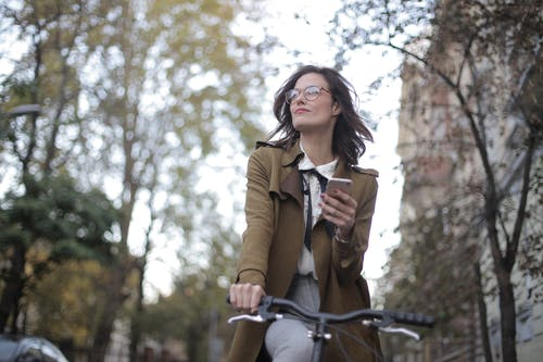 Woman in Brown Coat Riding Bicycle During Daytime
