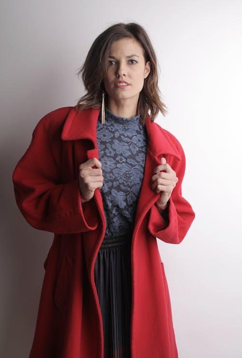 Wanita Berbaju Merah Berdiri Dekat Dinding Putih