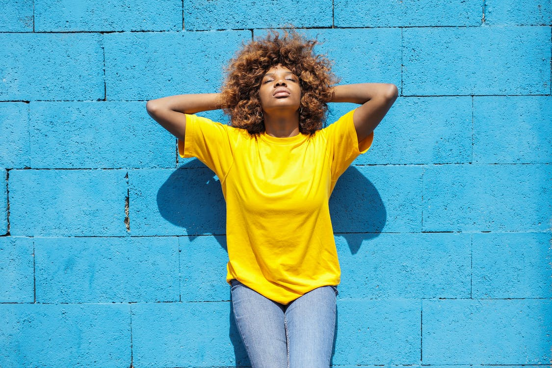 A Lady in Yellow Shirt Leaning Against Blue Brick Wall