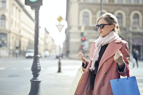 Woman in Pink Coat Holding Shopping Bags