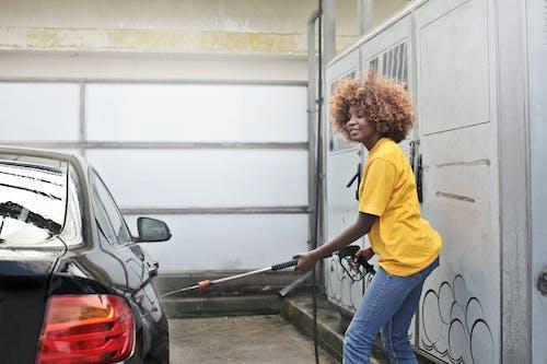 Woman in Yellow Shirt Washing a Black Vehicle