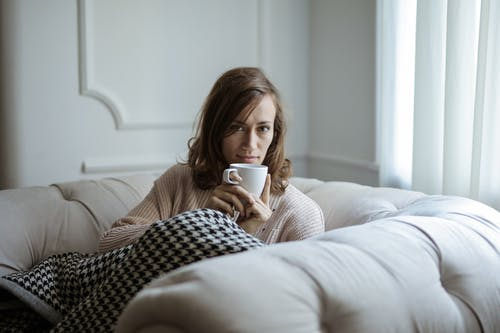 Photo of a Woman Drinking Coffee on White Ceramic Mug