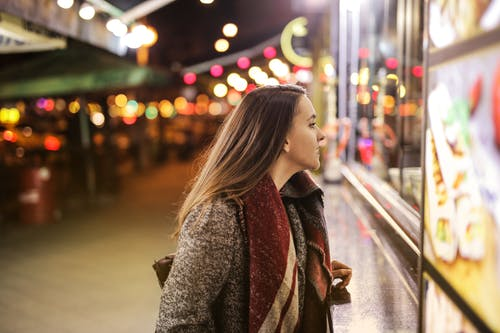 Woman in Brown Coat Standing on Sidewalk during Night Time