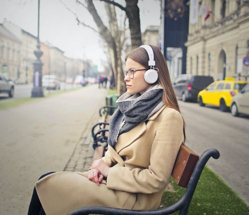 Woman Sitting On Black and Brown Bench Listening to Music