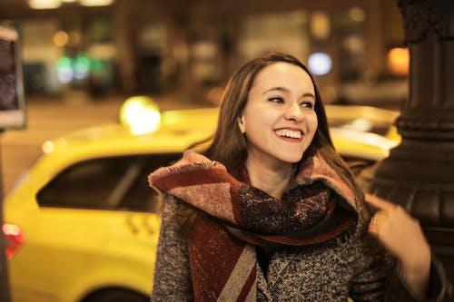 Woman Wearing Scarf Standing Near Yellow Taxi