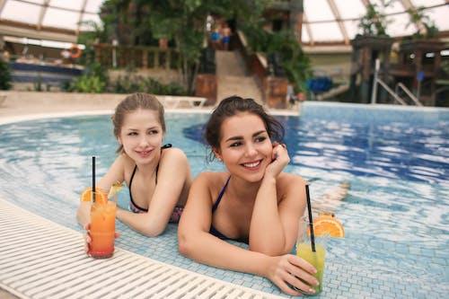 Deux Femme En Bikini Se Penchant Au Bord De La Piscine