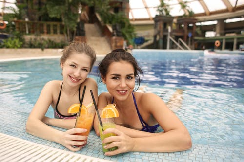 Two Women in Swimming Pool Holding Cocktail Drink