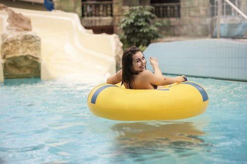 Woman in Yellow Inflatable Ring on Swimming Pool