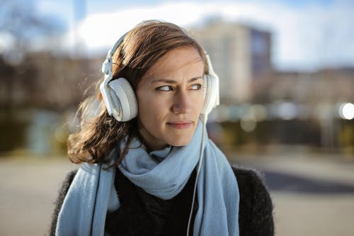 Woman in Black Sweater Listening To Music