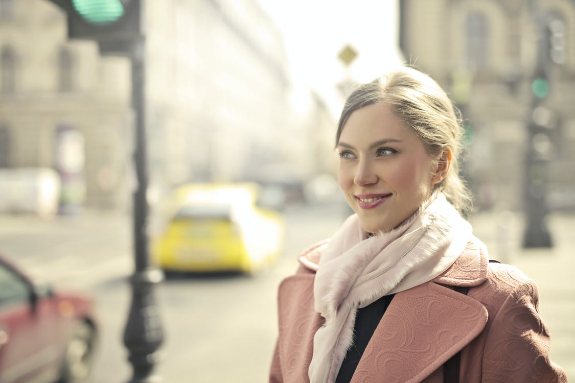 신호등 근처에 서있는 핑크 코트에 여자
