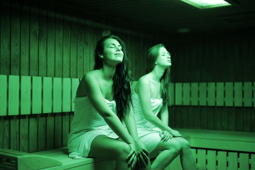 Siblings Sitting On Wooden Bench On Sauna