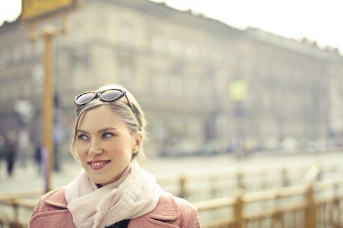 Smiling Woman in Pink Coat Wearing Black Framed Eyeglasses