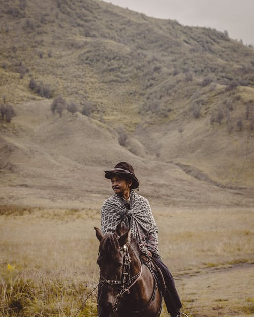 Man in Brown Cowboy Hat Riding A Horse
