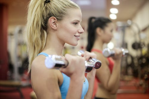 Woman in Blue Active Wear Lifting Dumbbells
