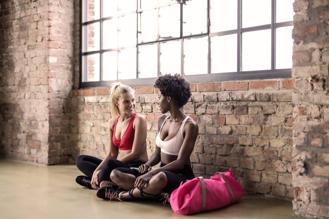 Two Women Sitting on Floor Beside Brick Wall
