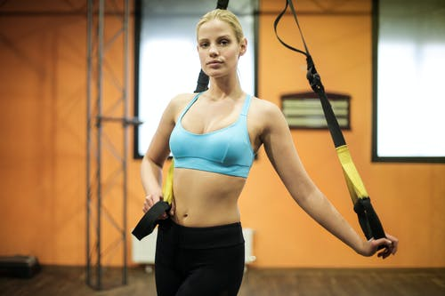 Woman in Blue Sports Bra and Black Leggings Holding Yellow and Black Strap