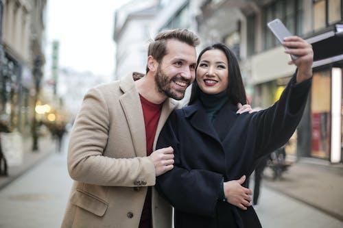 Man in Brown Coat Smiling Beside Woman in Black Coat Taking Selfie