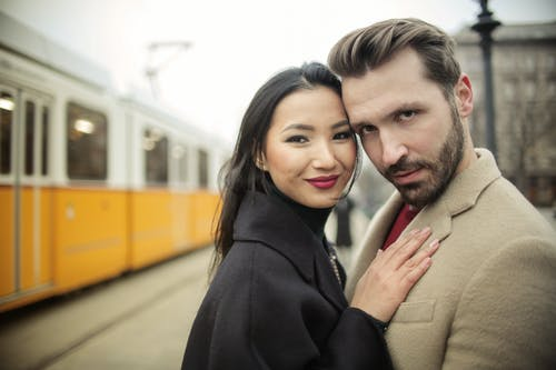 Man and Woman Standing beside Yellow Train