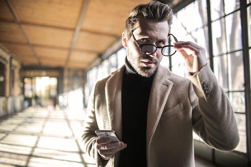 Man in Brown Suit Coat Holding His Black Frame Eyeglasses