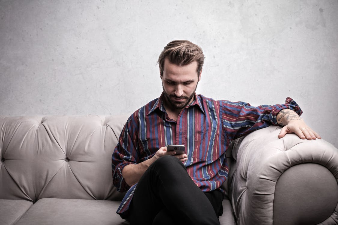 Man in Red and Blue Long Sleeve Using Smartphone