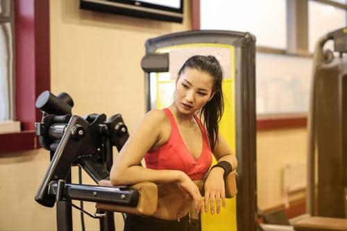 Woman in Red Sport Bra Standing on Black  Exercise Equipment