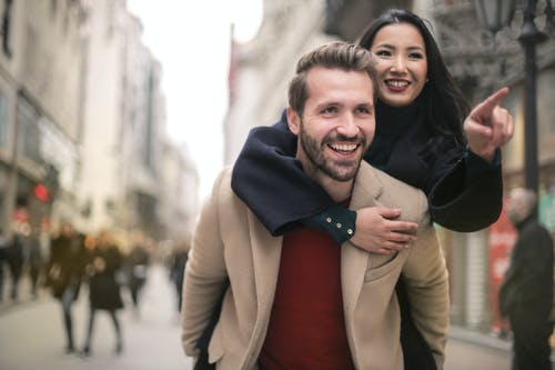 Man in Brown Coat Smiling Beside Woman in Black Coat