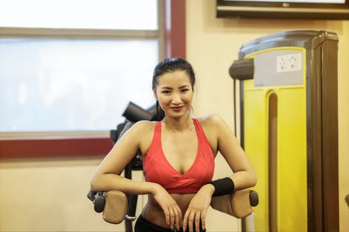 Woman in Red Sport Bra Standing in a Exercise equipment